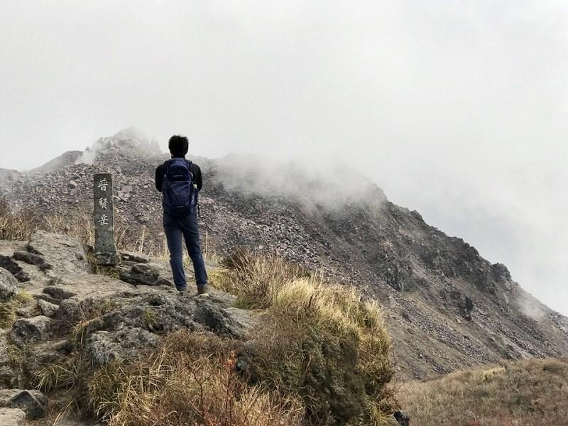 男性が雲仙普賢岳の頂上に立っている様子