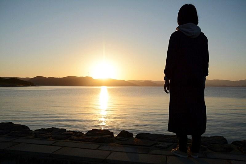平戸市の千里ヶ浜海水浴場で、女性が日の出を見ている様子