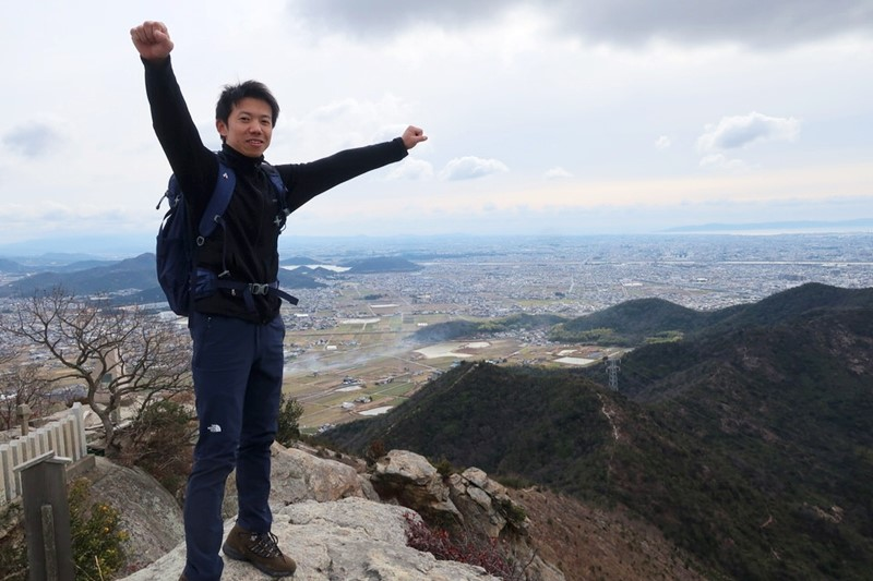 高御位山の頂上でガッツポーズをする男性の様子