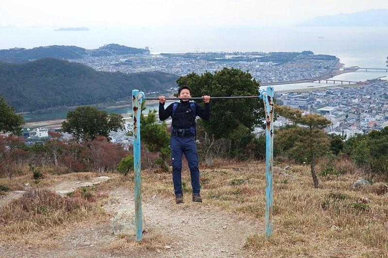 男性が雄鷹台山の頂上にある鉄棒で遊んでいる様子