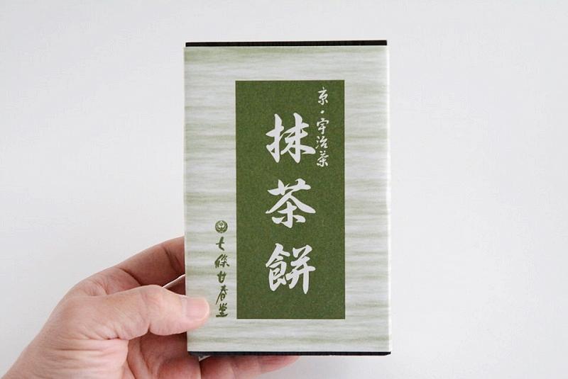 七條甘春堂「抹茶餅」の外箱を手に持っている様子