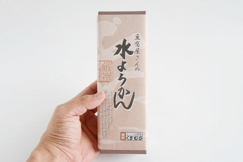 くすむら「豆腐屋さんの水ようかん」の箱を手に持っている様子