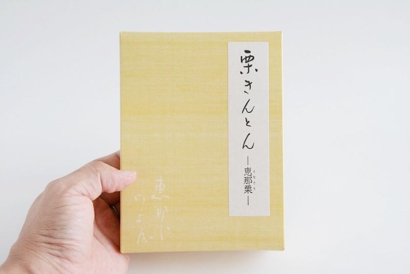 恵那川上屋栗きんとんの箱を手に持っている様子