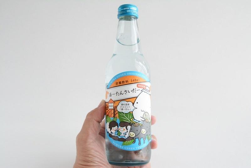 湯~たんサイダーの瓶を手に持っている様子