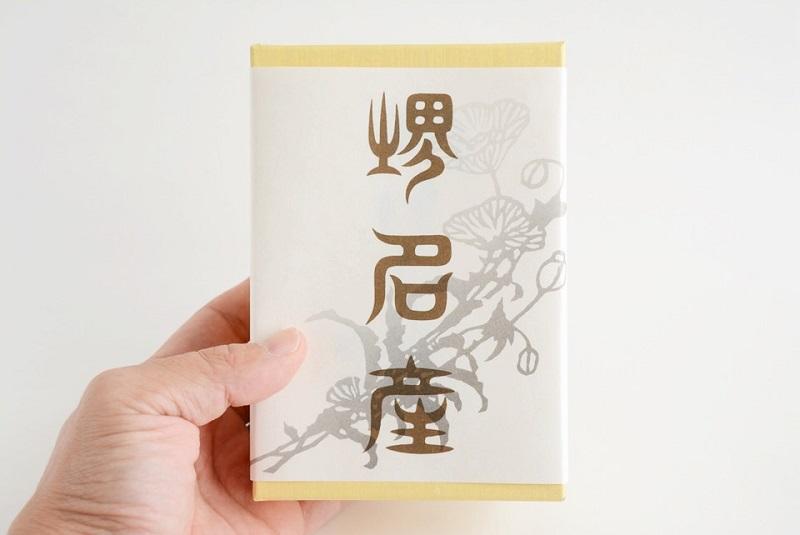 小島屋泰芳「けし餅」の箱を持っている様子
