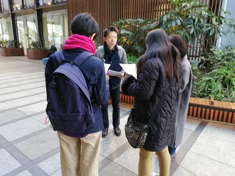 ツアーガイドが3人の女性にパンフレットを配り説明している様子
