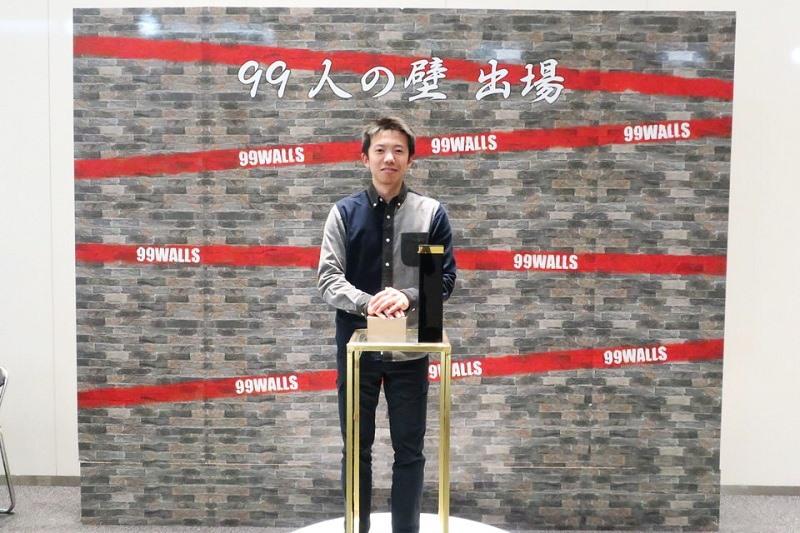 99人の壁のセットに立っている男性