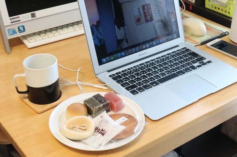 机に並べたノートパソコンとお菓子をのせた皿