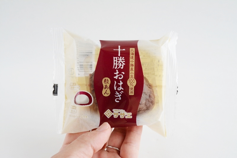 サザエ食品の十勝おはぎ(粒あん)の個包装を手に持っている様子